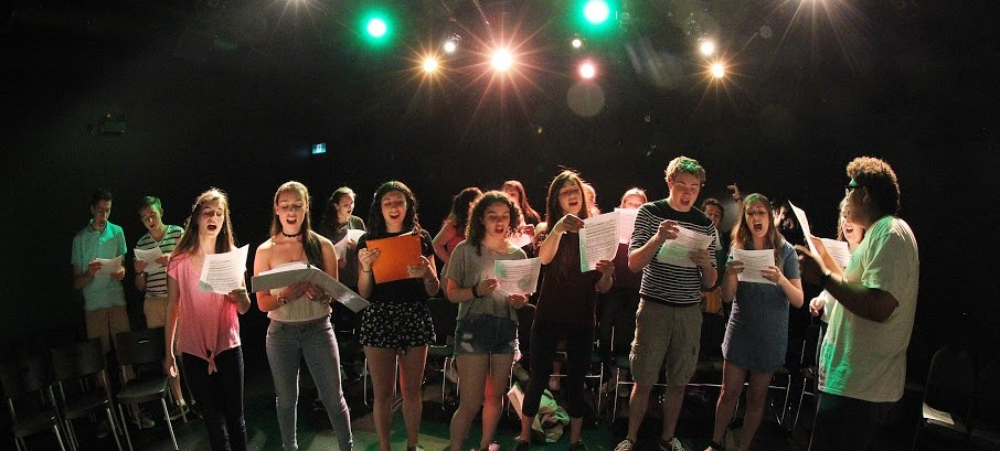 Teenage students singing from sheet music